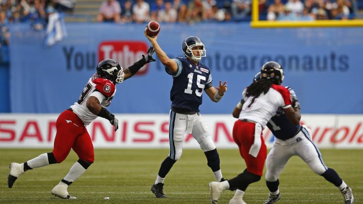 Toronto Argonauts' Ray throws a pass under pressure from Calgary Stampeders' Hughes during CFL game in Toronto