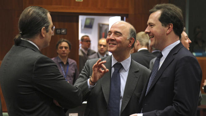 French Finance Minister Pierre Moscovici, center, talks with Swedish Finance Minister Anders Borg, left, and British Chancellor of the Exchequer George Osborne, during the EU finance ministers meeting, at the European Council building in Brussels, Tuesday, May 14, 2013. European Union finance ministers seek ways to cut down on tax evasion - action British Chancellor George Osborne said is particularly important in current circumstances. (AP Photo/Yves Logghe)