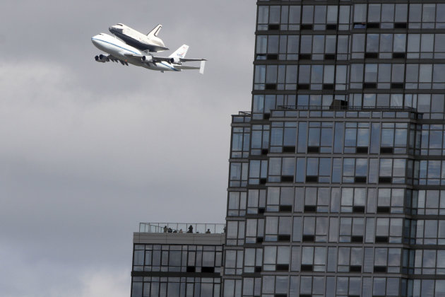 People watch from the balcony of a building as the space shuttle Enterprise, riding on the back of the NASA 747 Shuttle Carrier Aircraft, cruises over the Hudson river, Friday, April 27, 2012 in New York. Enterprise is eventually going to make its new home in New York City at the Intrepid Sea, Air and Space Museum. (AP Photo/Mary Altaffer)