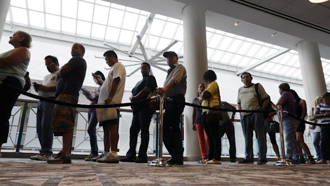 People wait in line to sign up for unemployment Wednesday, Sept. 3, 2014, in Atlantic City, N.J. Thousands of newly laid-off casino workers turned out at the Atlantic City Convention Center for a mass unemployment filing. The session Wednesday morning comes after a brutal weekend that saw more than 5,000 employees at the Showboat and Revel lose their jobs. (AP Photo/Mel Evans)