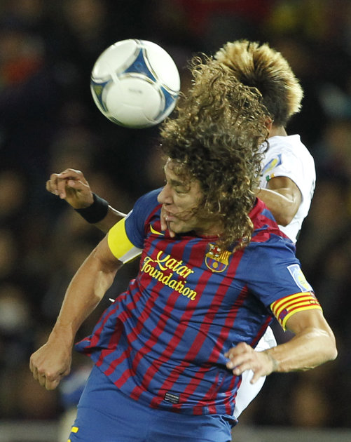 Spain's FC Barcelona defender Carles Puyol, foreground, and Brazil's Santos FC forward Neymar battle for a header during their final match at the Club World Cup soccer tournament in Yokohama, near Tok