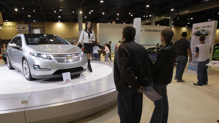 FILE - In this Nov. 7, 2010 file photo, Samantha Lozon of Grosse Pointe, Mich., stands next to the 2011 Chevrolet Volt, a rechargeable electric car, during the South Florida International Auto Show in Miami Beach, Fla. There's no guarantee GM can afford to continue to invest in electric vehicles or other green technologies.  And much like the Toyota with its Prius, GM probably won't make money on the Volt until the third or fourth generation. (AP Photo/Lynne Sladky, File)