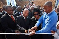 South African President Jacob Zuma (2nd left) helps Nelson Mandela's grandson (right) cut the ribbon to unveil a monument to commemorate the 50th anniversary of Mandela's capture by the apartheid police in Howick