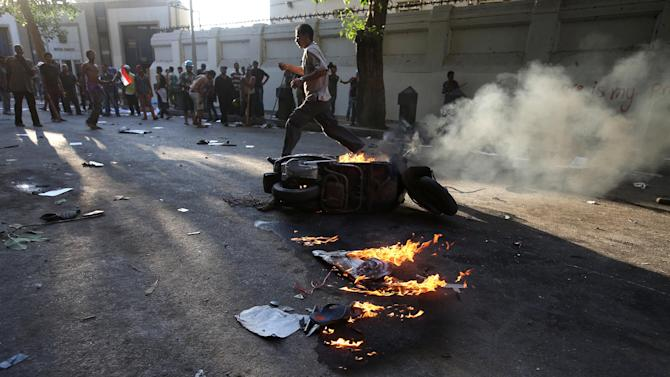 Opponents of ousted President Mohammed Morsi, gather near a burning scooter, that was set on fire during clashes with Morsi supporters, in Cairo, Egypt, Monday, July 22, 2013. On Monday, clashes broke out between Morsi supporters and opponents near Cairo's Tahrir Square and in the city of Qalioub on the capital's outskirts, where at least one person was shot to death, security officials said. (AP Photo/Hussein Malla)