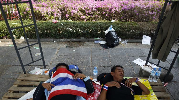 Anti-government protesters sleep outside the Government house where they gathered in Bangkok
