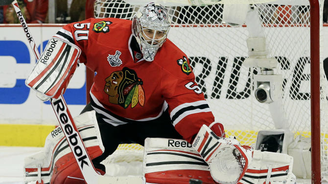 Chicago Blackhawks goalie Corey Crawford (50) gloves the puck on a shot attempt by the Boston Bruins during Game 2 of the NHL hockey Stanley Cup Finals, Saturday, June 15, 2013, in Chicago. (AP Photo/Nam Y. Huh)