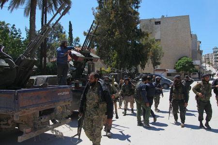 Nusra Front fighters walk with their weapons in Jisr al-Shughour town, after they took control of the area