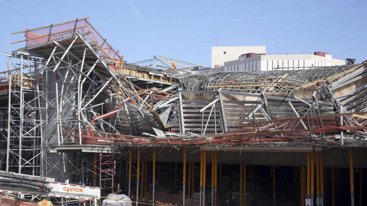 A worker walks near the site where section of a parking structure under construction collapsed Friday March 28, 2014 in Los Angeles. No one was trapped or hurt, authorities said. (AP Photo/Nick Ut)