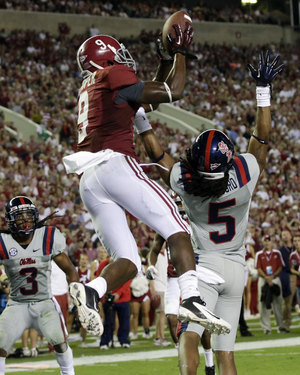Alabama wide receiver Amari Cooper (9) catches a 12-yard touchdown pass as Mississippi defensive back Frank Crawford (5) and defensive back Charles Sawyer (3) defend in the first half of an NCAA college football game at Bryant-Denny Stadium in Tuscaloosa, Ala., Saturday, Sept. 29, 2012. (AP Photo/Dave Martin)
