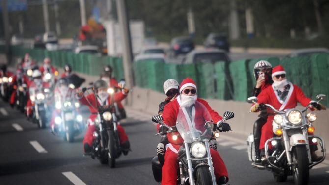 Owners of Harley-Davidson motorcycles wearing Santa Claus costumes ride along a street to give presents to elders at a nursing home during a promotional event celebrating Christmas in Guangzhou