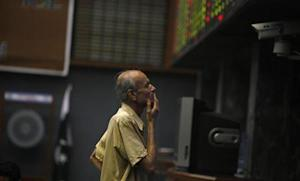 A man reacts as he monitors share prices during a trading session at the Karachi Stock Exchange