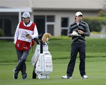 Rory McIlroy of Northern Ireland (R) eats a sandwich with his caddie on the 18th green before taking his final shot of the tournament during second round play in the Honda Classic PGA golf tournament