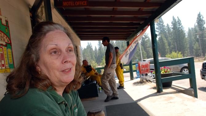 Beth Glenn, whose family owns the store, motel, restaurant and other commercial operations in the tiny Northern California mountain town of Mineral talks Thursday, Aug. 23, 2012 about living with a massive wildfire just 6 1/2 miles west of town. She said she is not nervous, coming from a family of firefighters, and lived for many years with the fires in Southern California. (AP Photo/Jeff Barnard)
