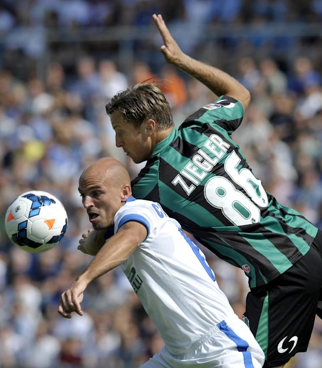 Sassuolo's Reto Ziegler, of Switzerland, right, vies for the ball with Inter Milan's Esteban Cambiasso, of Argentina, during their Serie A soccer match at Reggio Emilia's Mapei stadium, Italy, Sunday,