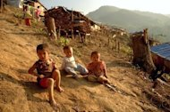 "Kachin children play outside wooden shacks at the N-Hkawng Pa Internally Displaced People's camp outside Mai Ja Yang, in Kachin province. Amnesty International accused Myanmar's army of ""indiscriminate attacks"" against minority civilians in Kachin that amount to ""war crimes"""