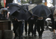 Office workers lean their umbrellas as they walk against the strong wind and rain caused by Typhoon Sanba in Seoul, South Korea, Monday, Sept. 17, 2012. (AP Photo/Lee Jin-man)