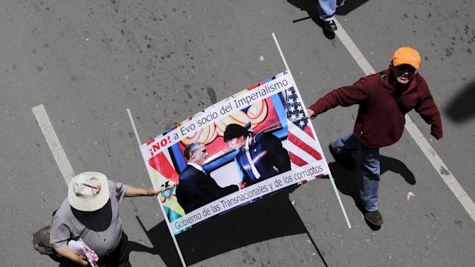 Demonstrators hold up a banner with the images of U.S. President Barack Obama and his Bolivian counterpart Evo Morales during a protest rally in the centre of La Paz