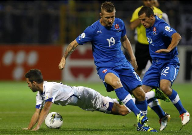 Bosnia's Pijanic fights for the ball with Slovakia's Kucka and Pecovsky during their 2014 World Cup qualifying soccer match in Zenica
