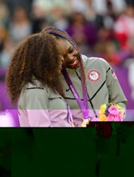 US Serena Williams (L) and Venus Williams stand on the podium after receiving their gold medals for winning the London 2012 Olympic Games women's doubles tennis tournament, at the All England Tennis Club in Wimbledon, southwest London