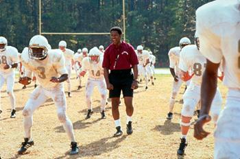 Academy Award? winner Denzel Washington (center) stars as high school football coach Herman Boone who, in 1971, is caught in the middle of integrating an all-black and all-white football team and faces the prejudice and intolerance of a small Virginia town in Walt Disney Pictures' Remember The Titans