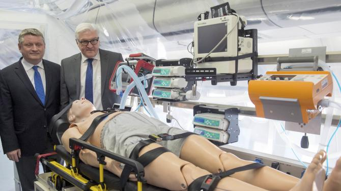 German Foreign Minister Steinmeier and Health Minister Hermann Groehe stand in isolation unit of new Medevac plane in Berlin