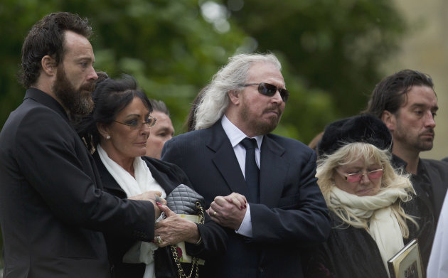Barry Gibb, center, and Robin Gibb&#39;s wife Dwina Gibb, right, who holds an order of service, react at the graveside during the burial of Robin Gibb outside St Mary&#39;s Church in Thame, England, Friday, June 8, 2012. Robin Gibb a member of the iconic Bee Gees pop group died May 20, after a long battle with cancer.(AP Photo/Alastair Grant)