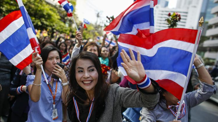 Anti-government protesters react during a rally at a major business district in Bangkok