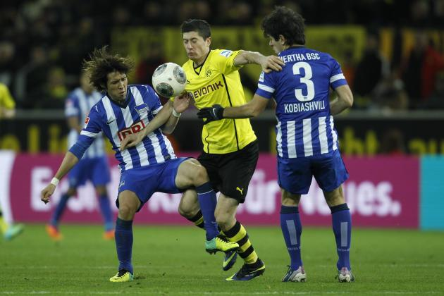 Hertha Berlin's Hosogai and Kobiashvili challenge Borussia Dortmund's Lewandowski during the German first division Bundesliga soccer match in Dortmund