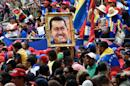 People hold a portrait of former Venezuelan president Hugo Chavez during a ceremony commemorating the second anniversary of his death in Caracas on March 5, 2015
