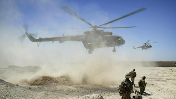 FILE - In this July 8, 2011 file photo released by the Australian Defense Force, members of the National Interdiction Unit (NIU) and the Special Operations Task Group (SOTG) await the arrival of two Mi-17 helicopters in Kandahar, Afghanistan. To outfit Afghanistan's security forces with new helicopters, the Pentagon bypassed U.S. companies and turned instead to Moscow for dozens of Russian Mi-17 rotorcraft at a cost of more than $1 billion. Senior Pentagon officials assured skeptical members of Congress they'd made the right call, pointing repeatedly to a top-secret 2010 study they said named the Mi-17 as the superior choice. (AP Photo/Australian Defense Force, File)