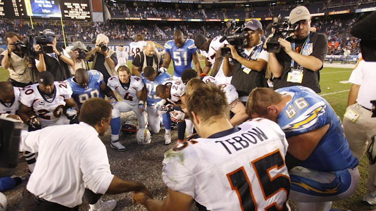 Denver Broncos quarterback Tim Tebow prays with members of both teams after their overtime win against the San Diego Chargers in an NFL football game on Sunday, Nov. 27, 2011, in San Diego. (AP Photo/Lenny Ignelzi)