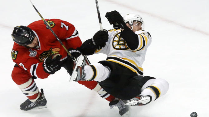 Boston Bruins left wing Daniel Paille, right, shoots as he collides with Chicago Blackhawks defenseman Brent Seabrook during the third period of Game 1 in their NHL Stanley Cup Final hockey series on Wednesday, June 12, 2013, in Chicago. (AP Photo/Charles Rex Arbogast)