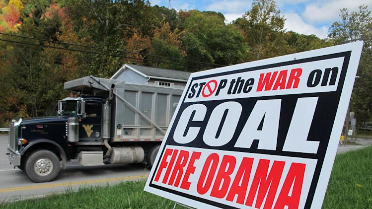 "A truck passes a political sign in a yard in Dellslow, W.Va., on Oct. 16, 2012. Rhetoric about the administration's alleged ""war on coal"" has come to dominate conversation this campaign season.  Once, coal miners were literally at war with their employers. Today, their descendants are allies in a rhetorical war playing out across eastern Kentucky, southwestern Virginia and all of West Virginia. The message: They now face a common enemy _ the federal government, especially the president and the Environmental Protection Agency. (AP Photo/Vicki Smith)"