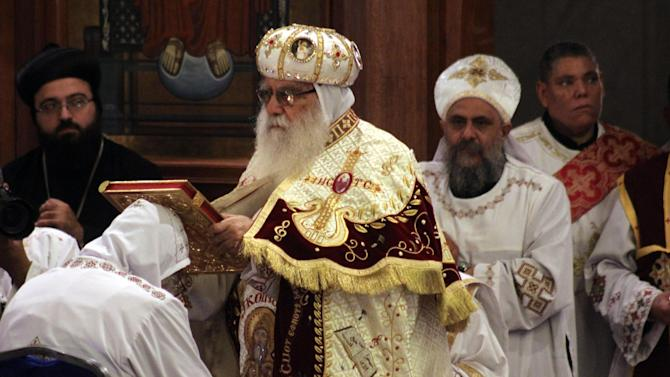 Bishop Bakhomious, the acting head of the Coptic Church, places a Bible on the head of soon to be Pope Tawadros II during an elaborate ceremony lasting nearly four hours, attended by the nation's Muslim prime minister and a host of Cabinet ministers and politicians, enthroning the new pope in the Coptic Cathedral in Cairo, Egypt, Sunday, Nov. 18, 2012. Tawadros II did not address the televised ceremony, but had a brief speech read on his behalf by one of the church's leaders in which he pledged to work for the good of Egypt, with its Muslims and Christians alike. (AP Photo/Roger Anis, El Shorouk Newspaper) EGYPT OUT