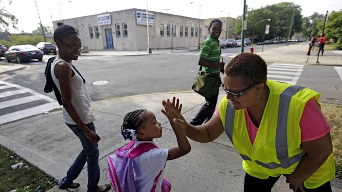 """Safety Guard Renee Green high-fives Demari Hill, 5, as she heads to Gresham Elementary School with her parents Destiny and Anthony Hill on her first day of kindergarten classes on Monday, Aug. 26. 2013, in Chicago. Thousands of students will walk newly designated """"Safe Passage"""" routes after CPS announced in May it would close about 50 schools and programs. Workers hired to help students get to and from school safely will be stationed along those routes, as well as police, firefighters and even public library security guards. (AP Photos/M. Spencer Green)"""