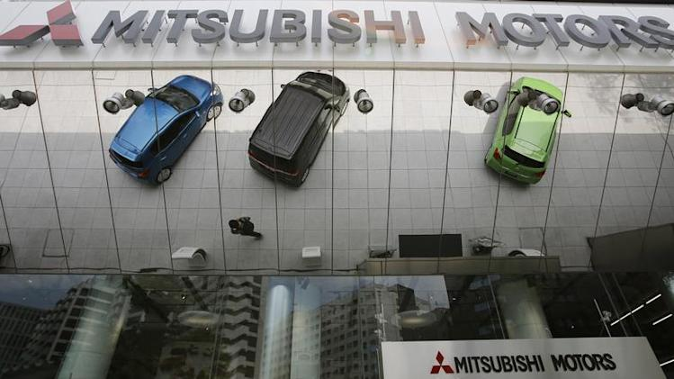 Mitsubishi Motors Corp's vehicles and a passer-by are reflected on an external wall at the company headquarters in Tokyo