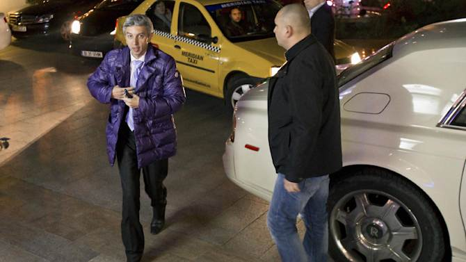 In this photo taken on Dec. 4, 2012, Dan Diaconescu, the leader of the populist People's Party walks from his Rolls Royce, in Bucharest, Romania. Diaconescu, a media tycoon has emerged as a key player in Romania's bitterly contested parliamentary election. Diaconescu's party is running third in Sunday's vote, according to polls. The gray-haired, multimillionaire talk show host from Romania's disenfranchised south appears to be tapping into widespread discontent with traditional political parties seen as arrogant, sniping and corrupt. Romania will hold parliamentary elections on Dec. 9, 2012. (AP Photo/Vadim Ghirda)