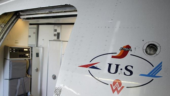 "In this Thursday, Sept. 27, 2012, photo, the US Airways 'Heritage"" logo is shown by the door of a jet parked at the Charlotte/Douglas International airport in Charlotte, N.C. Patched together from several scrappy regional carriers on the brink of bankruptcy, US Airways has often been ridiculed within the aviation industry and remains a perennial afterthought among travelers. But it hopes to shed that image by merging with the larger American Airlines, in a deal which will catapult the two to the top of the industry. (AP Photo/Chuck Burton)"