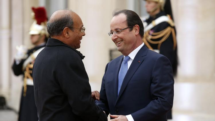 France's President Hollande greets Tunisia's President Marzouki in the courtyard of the Elysee Palace at the start of the Elysee Summit for Peace and Security in Africa, in Paris