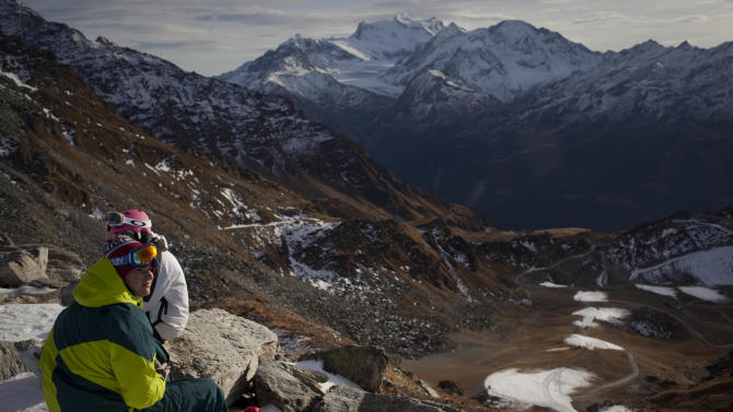 Skiers rest on a mountain overlooking snow-free slopes at the ski resort of Verbier, in the south-western part of Switzerland, Thursday, Dec 1, 2011.  Unusually warm, dry weather has Switzerland's ski resorts on edge, threatening the traditional start of the ski season on the first weekend of December. (AP Photo/Anja Niedringhaus)