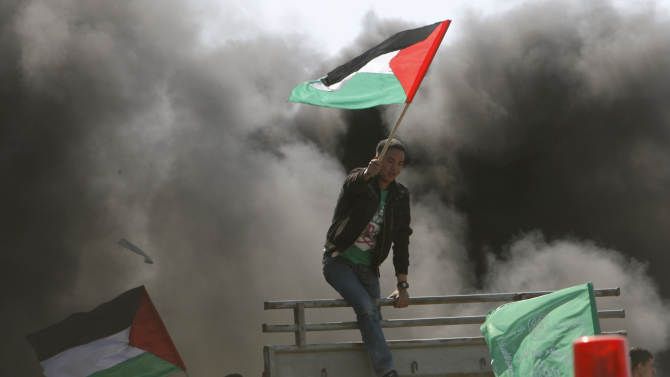 """Demonstrators wave a Palestinian flag during a rally marking """"Land Day"""" in Beit Hanoun, northern Gaza Strip, Friday, March 30, 2012. The """"Land Day"""" rallies are an annual event marked by Israeli Arabs and Palestinians in the West Bank and Gaza who protest what they say are discriminatory Israeli land policies.(AP Photo/Adel Hana)"""