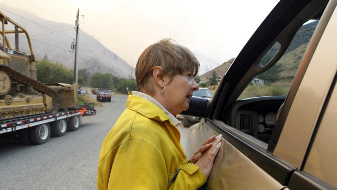 Susan Peterson, a public information officer with the U.S. Forest Service, talks with a local resident about a wildfire there near the end of Number 1 Canyon Road Monday, Sept. 10, 2012, near Wenatchee, Wash. Crews in central Washington and Wyoming worked Monday to protect homes from two of the many wildfires burning throughout the West as a destructive fire season stretches into September with no relief expected from the weather anytime soon. The National Weather service issued red-flag warnings for wide swaths of eastern Washington and Oregon, Idaho, Montana and all of Wyoming, meaning conditions could exacerbate blazes. (AP Photo/Elaine Thompson)
