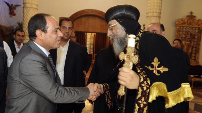 Egypt's former military chief Abdel-Fattah el-Sissi, shakes hands with Coptic Pope Tawadros II at Cairo's St. Mark's Cathedral, seat of the Coptic Orthodox Pope, in Cairo, Egypt, Saturday, April 19, 2014. El-Sissi on Monday took the final formal step to run in next month's presidential election, submitting to the election commission eight times the number of signatures required. He is widely expected to win. (AP Photo/Girgis Mahboub, Office of the Coptic Pope)