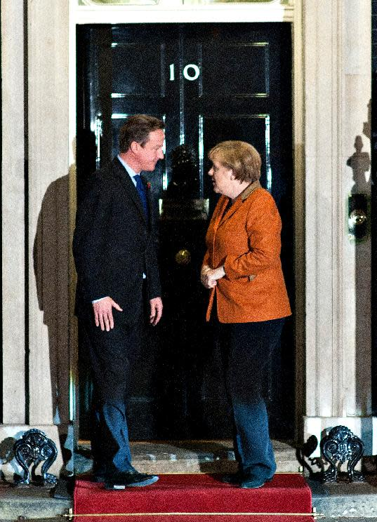 Britain's Prime Minister David Cameron, left, talks to German Chancellor Angela Merkel, right, as they pose for the media before their meeting at 10 Downing Street, in London, Wednesday, Nov. 7, 2012. The Prime Minister said at a recent EU summit in Brussels that he would veto any proposal for the next seven-year budget framework that went above a freeze on the current position, this, in turn, allegedly left the German Chancellor prepared to scupper a summit of European leaders due on 22-23 November on the EU budget unless David Cameron withdraws the threat of a blanket veto. (AP Photo/Bogdan Maran)