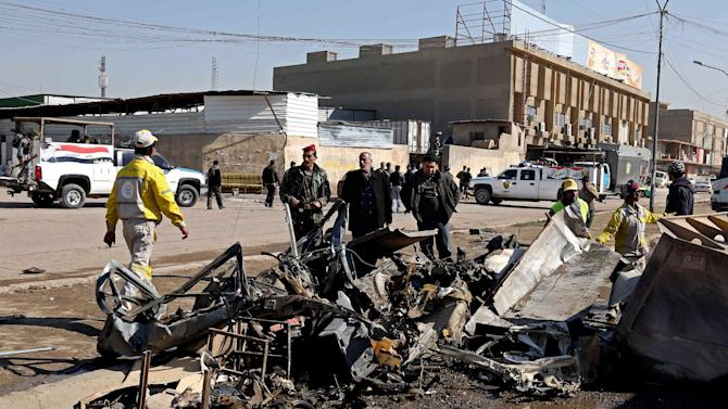 People and security forces inspect the site of a car bomb attack in Baghdad's Karrada neighborhood, Iraq, Thursday, Feb. 6, 2014. Iraqi officials say a string of car bombings has hit commercial areas in Baghdad, killing and wounding scores of people. (AP Photo/Khalid Mohammed)