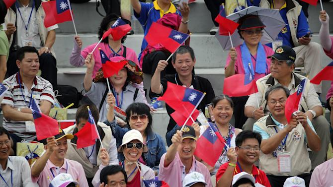 Spectators wave the national flag as they wait for the start of a massive parade to mark the 70th anniversary of the end of WWII, at the military base in Hsinchu, northern Taiwan, Saturday, July 4, 2015. Taiwan marched out thousands of troops and displayed its most modern military hardware Saturday to spotlight an old but often forgotten claim that its forces, not the Chinese Communists, led the campaign that routed imperial Japan from China 70 years ago. (AP Photo/Wally Santana)
