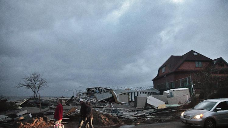 People walk through the houses destroyed in the aftermath of yesterday's storm surge from superstorm Sandy, Tuesday, Oct. 30, 2012, in Coney Island's Sea Gate community in New York. (AP Photo/Bebeto Matthews)