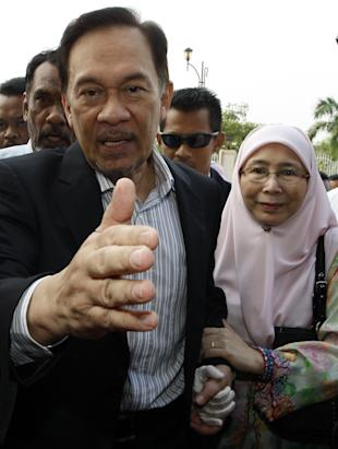 Malaysian opposition leader Anwar Ibrahim, left, and his wife Wan Azizah arrive at a courthouse in Kuala Lumpur, Malaysia, Monday, May 16, 2011. Malaysia's High Court will decide on Monday whether to dismiss the sodomy charge against Anwar or order his lawyers to start calling defense witnesses. Anwar faces up to 20 years in prison if convicted of sodomizing a male former aide in 2008.