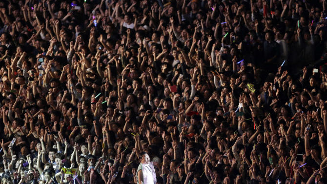 """FILE - In this Oct. 4, 2012 file photo, South Korean rapper PSY, who sings the popular """"Gangnam Style,"""" performs during his concert in front of Seoul City Hall in Seoul, South Korea. As """"Gangnam Style"""" gallops toward 1 billion views on YouTube, the first Asian pop artist to capture a massive global audience has gotten richer click by click. So too has his agent and his grandmother. But the money from music sales isn't flowing in from the rapper's homeland South Korea or elsewhere in Asia. With one song, 34-year-old Park Jae-sang — better known as PSY — is set to become a millionaire from YouTube ads and iTunes downloads, underlining a shift in how money is being made in the music business. (AP Photo/Lee Jin-man, File)"""
