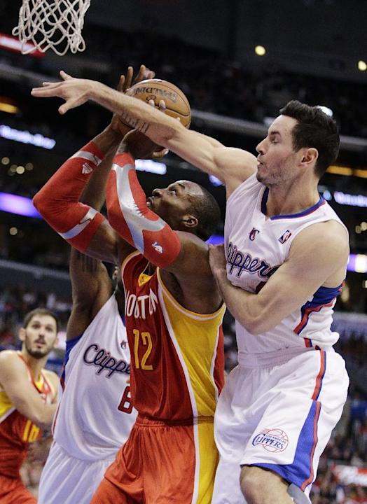 Houston Rockets' Dwight Howard, left, is defended by Los Angeles Clippers' J.J. Redick during the second half of an NBA basketball game on Monday, Nov. 4, 2013, in Los Angeles. The Clippers won 137-11